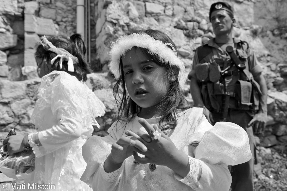 Purim in Hebron XIV: The Hebronite BrideJewish settlers celebrate the Purim holiday under heavy Israeli  military guard on 20 March in the divided West Bank city of Hebron. In this photo, Jewish girls dressed as brides stand before an Israeli Border Police officer.