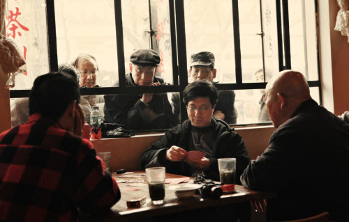 Men playing cards in a smoky teahouse inside of Shanghai's Luxun Park on a rainy Sunday afternoon. 2011