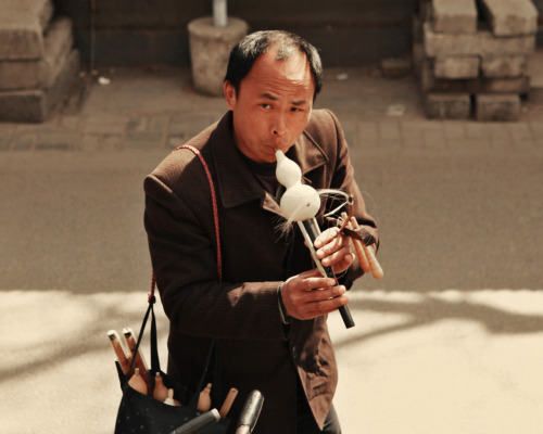 a flute peddler showcases his talent in Beijing's historic Hutong Village. 2011