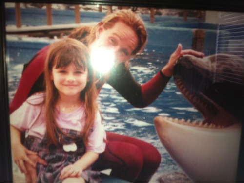 parkavenue:  This is me at age six with Taima, one of the Orca Whales at Sea World Orlando. I grew up around these animals. One night, after the park had closed, while my father finished up his work, I played catch with a fish and a 14,000 pound whale nicknamed Tilly, the whale now notorious for the incident last year with Dawn Brancheau. I would throw the fish into the main tank; he would let it float to the bottom, swim down and pick it up delicately, rub it against the glass in front of my hands, and toss it back over the wall for me to catch again. I grew up knowing all their names. I knew how much the trainers loved them; and how they never forgot that they were wild animals. I knew that no one was allowed to swim with Tilly; not because he was violent, but because he had witnessed two other whales' violence at a young age and Sea World would not take the risk of finding out if he had been traumatized. I knew that the morning when they found him with a man on his back, dead, he was swimming around his tank frantically making distress calls. A mentally ill man had climbed into his tank overnight, died of hypothermia, and Tilly didn't know what to do, other than lift him to air where he wouldn't drown. I knew Dawn. And I know that seeing PETA protesting outside Sea World this morning would have broken her heart. But most of all, I know that an animal the size of an elephant that can give kisses to the cheek of a six year old girl is not a monster. Staying off Tumblr until the heat from Sea World's accusers dies down; the misinformation and ignorance tears me apart. Edit: please, please reblog this. The article from the daily what has come up on my dash too many times to not have a rebuttal.