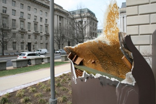 "WaPo:  Did vandalism or wind claim an IRS sign downtown? The facts: A sign outside the Internal Revenue Service headquarters was beheaded last month. The hypothesis: A District resident, furious about paying federal taxes while being denied equal representation in Congress, took a sledgehammer to a small symbol of America's most mind-boggling constitutional inconsistency. The official IRS response: The wind did it. You know the sign. Or you know the type. If you work for or near a federal agency, you see them everywhere downtown: The signs are thin and 10 feet tall, with a slight convex curve toward their tops, like a legion of shadowy soldiers with poor posture. White lettering spells out the agency name on a black surface bleached by the sun. The official name for them is ""molded fiberglass monolithic facility identification signs"" and they were installed around the city in the mid-to-late-'70s. They look bland and procedural and definitely of the post-Watergate era. And they look and feel sturdy. Like it would take a hurricane to snap one in half. Winds did reach 65 mph on Feb. 25 in the D.C. area, and the IRS says it has security footage of the ensuing decapitation-by-Mother Nature at the southwest corner of 12th Street and Constitution Avenue NW. They will not show the footage to us. Engineering professors at the universities of Maryland and Virginia say that wind cannot be ruled out as a culprit. […] But perhaps we're letting our imagination run away with itself. No one was hurt at 12th and Constitution. It's just a sign. An ugly sign, at that. The damage is actually an improvement — it reveals a far more interesting interior of plywood and honeycombed cardboard and a strange fibrous membrane that feels like horsehair. Who's even responsible for these signs? A man named David Pesanelli. He's 73. He lives in Rockville. In the '70s, he sketched the curved design on a cocktail napkin. He thought it was more graceful than the usual vertical slabs that were plunked in front of buildings in the Washington area. His design firm refined the concept for use outside the former Psychiatric Institutes of America on MacArthur Boulevard NW. Within a year, he noticed a ""poor interpretation"" of his design on display outside federal buildings downtown. ""I was kind of horrified when I saw it,"" says Pesanelli, who closed his firm in the late '80s and has been a communications and environment consultant since. The company that manufactured the signs on MacArthur Boulevard had co-opted his unpatented concept for its federal contract. The result, in his opinion, was a more rigid, brutalist version of his initial notion. And they popped up all around town. ""Some of the buildings themselves are kind of brutal,"" Pesanelli says. ""They're massive, clunky, and they're projecting all kinds of imagery of overweening power. In a funny way, they may be a fairly appropriate match for the buildings."" But no match for a gust of wind. Or a sledgehammer, if you're a romantic."
