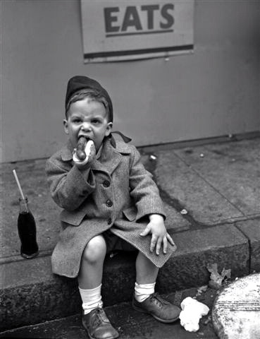 Three-year-old eats a hot dog on a curb in East Village, 1950Photographed by Nat Fein