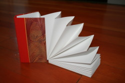Book arts displaying the following bindings: flat back, gary frost, accordion, and single signature stitch book with clamshell box.