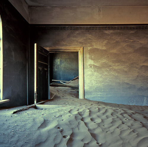 hrtbps:  Kolmanskop is a ghost town in southern Namibia, a few kilometres inland from the port of Lüderitz. In 1908, Lüderitz was plunged into diamond fever and people rushed into the Namib desert hoping to make an easy fortune. Within two years, a town, complete with a casino, school, hospital and exclusive residential buildings, was established in the barren sandy desert. But shortly after the drop in diamond sales after the First World War, the beginning of the end started. During the 1950's the town was deserted and the dunes began to reclaim what was always theirs. (photo / words)