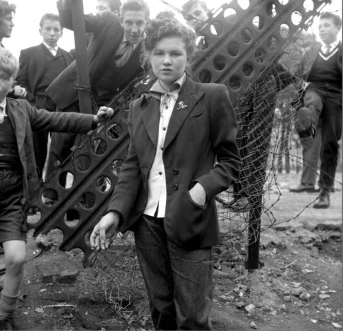 "14 year old Jean Rayner surrounded by young aspiring Teddy Boys on a bombsite, January 1955  Teddy Girls (Judies) The original Teddy Girls, like the Teddy Boys started in London. These were a group of feisty young women who were set on creating an identity of their own. Their choice of clothes wasn't only for aesthetic effect: these girls were collectively rejecting post-war austerity. These were young working-class women, often from Irish immigrant families who had had settled in the poorer districts of London - Walthamstow, Poplar and North Kensington. They would typically leave school at 14 or 15, work in factories or offices.The Teddy girls would spent their free time buying or making their trademark clothes - pencil skirts, rolled-up jeans, flat shoes, tailored jackets with velvet collars, coolie hats and long, elegant clutch bags. It was head-turning, fastidious dressing, taken from the fashion houses of the time, which had launched haute-couture clothing lines recalling the Edwardian era. Soon the fashion had leapt across the class barrier, and young working-class men and women in London picked up the trend. The Teddy Girls didn't care that their outfits shocked their families, as long as they were noticed among their peers. One of the original Teddy Girls famously photographed by Ken Russell in 1955, Rose Shine (then Rose Hendon) comments:  ""We got dressed up because it was always the Teddy Boys who got the look-in. We weren't being noticed by them"".  Rose, a 66-year-old grandmother in 2006 and proud to have been one of the first teddy girls states:  ""It was our fashion that we made up.""  These young, working-class women were the first generation of their social stratum and gender to express their financial independence and fashion acumen in such a forthright style. The settings of many of Ken Russell's 1955 pictures show the down-at-heel and often bomb-blasted neighbourhoods they hailed from, and serve as a fascinating counterpoint to the Teddy Girls gusty grace and sartorial inventiveness. (via edwardianteddyboyassociation )"