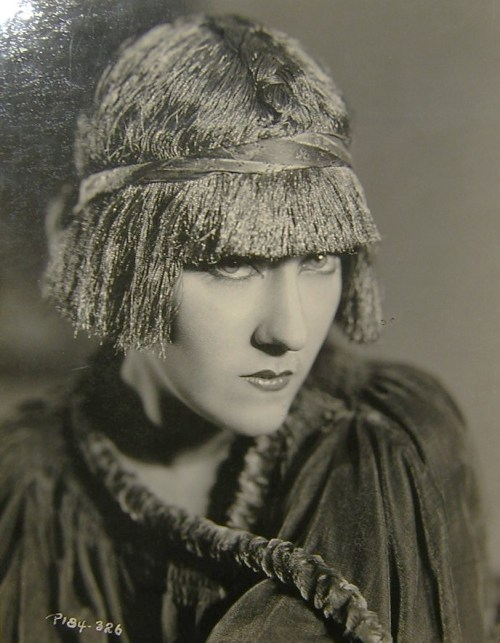 extranuance:  Gloria Swanson is wearing a french boudoir cap (Pioret design) to give the effect of a bobbed hair wig, done in gold metallic threads. c.1920s