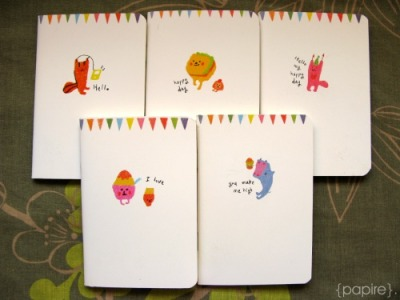 "Monomono Mini Notebook Designs: Music Cat | Burger Buns | Party Animal | IceCream Thingies | High Jump Whale Designed By: Iswas (Korea) Type: Notebook Dimension: (A4) 8.2 * 12.5 cm 64 Pages Alternating Ruled and Blank Pages Well, these are one of those cute notebooks that make you scream ""gyaa!"" immediately upon sight. Yes. It's THAT cute.  Featuring colourful bunting bordering the top of the front cover, coupled with lovely pencil colour illustrations 5 Designs available in this series SGD$3.00 each Detail:"