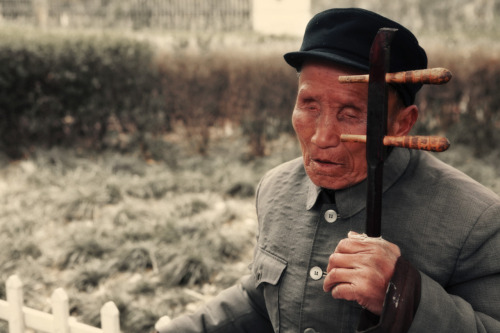 A blind man plays a traditional Chinese instrument on Moganshan road in Shanghai. 2011