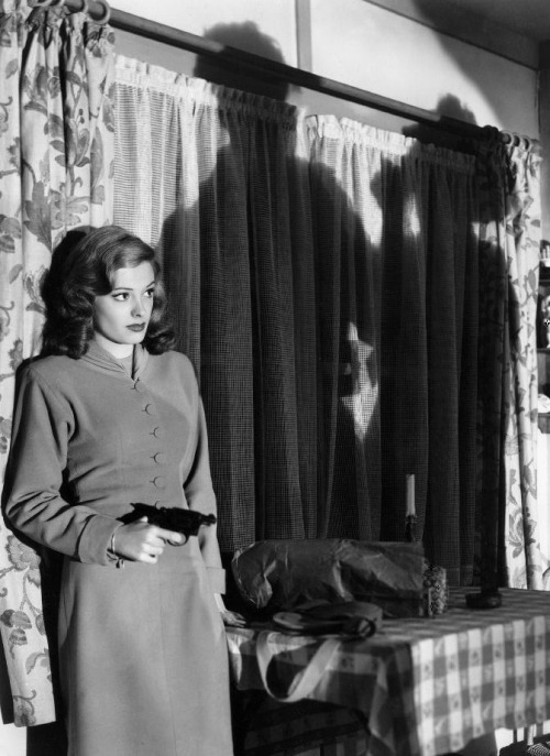"Jane Greer in Out of the Past (1947, dir. Jacques Tourneur) ""Zzjjane, do you know what ahm-pahs-eeve mean?"" [director Jacques Tourneur] asked the actress. ""Impassive? Yes."" ""No 'big eyes'. No expressive. In the beginning you act like a nice girl. But then, after you kill the man you meet in the little house, you become a bad girl. Yes? First half, good girl. Second half, bad.""  ""I get you,"" she said. That was his direction, Greer recalled. ""But I did throw in a few big eyes anyway. I couldn't help myself.""  Tourneur also discussed with her his plan for the character's wardrobe, something typical of his films' subtle, insidious visual design. ""At first you wear light colors. After you kill the man, darker colors. In the end, black."" -excerpted from Lee Server's Baby I Don't Care"