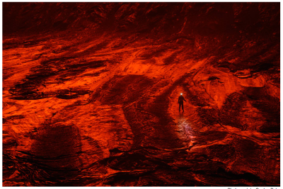 Not special effects or some movie set: A scientist walks along cooled lava inside of one of the world's most active volcanos. The red glow is a reflection of heated lava in the black, glassy surface. Photograph by Carsten Peter.