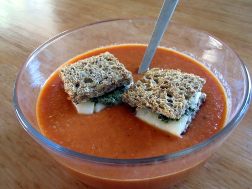 """Rock the Boat""- Creamy Roasted Tomato and Garlic Soup with Pesto Grilled Cheese Boats Early Sunday morning I had a lovely stroll through the Hollywood Farmer's Market.  The cool weather, great people watching and gorgeous produce made it a perfect ""farming"" day.  After the market, I got a huge craving for grilled cheese and tomato soup.  This combo is a huge favorite amongst folks and is the kind of meal that makes you feel like a kid again.  As for this kid, I decided my grilled cheese and tomato soup needed to grow up a bit.  What You Need (Serves 2): For the Soup: 4 Large Tomatoes (quartered) 4 Large Garlic Cloves (smashed) 1 Small Onion (quartered) Olive Oil Salt/Pepper 1/4 Cup Fresh Basil or 1/2 tsp. Dried Basil 2 tsp. Balsamic Vinegar. Heat oven to 400 degrees (on convection if you have it) 1. Combine tomatoes, garlic and onions in medium bowl.  Drizzle olive oil over the vegetables to coat.  Season with salt and pepper.  Pour the veggies onto baking sheet or casserole dish and place in heated oven. 2. Roast vegetables for 25 minutes. 3. Next, add the roasted vegetables, balsamic and basil into a blender and puree until it reaches your desired consistency.  Adjust seasonings to your liking. For the grilled cheese boats: 2 Slices of Bread (I used Sprouted Rye) 2 Tbsp. Pesto (I used pesto I bought from the Farmer's Market) 2 Slices of Cheese (I used Jarlsberg- but would suggest using Goat Cheese and Mozzarella) 1. Cut off the crusts of the bread then spread the pesto onto the slices and top with cheese.  Put the sandwich together and grill the sandwich in a greased pan or panini maker. 2. Slice the sandwich into quarters to form 4 mini grilled cheeses.  Place the mini sandwiches onto the portioned soup right before serving."