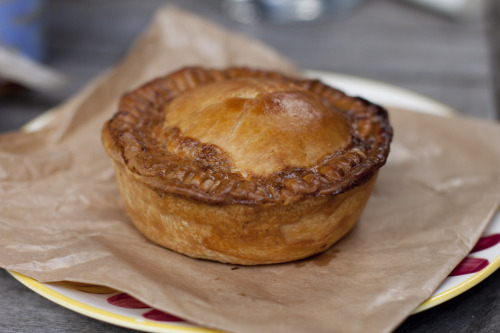 This is what an Australian meat pie looks like. Ok, so it's a posh one from this place, but my what deliciousness are to be found under that thick crusty exterior. Chunks of stewed beef and fresh diced vegetables - even thinking about pies like this makes me homesick. The only thing lacking was a squeeze of tomato sauce - remember that for next time, gracious hosts! I'm a fan of the ol' chicken vegetable or country chicken pie, too, but they're not for everyone. Purists will say the only true pie is the traditional meat pie of the Four n' Twenty/buy it at the footy variety. Apparently a former Australian pollie once called it the National Dish. But there are lots of variations on the theme. My dad is obsessed with steak and kindey pie (gross) and when I was little my mum taught me how to make a version of Shepherd's Pie which, weirdly, we called Hamburger Casserole. These are all things from home - the other home - way down the bottom of the earth.  Everyone has different ways of eating meat pies. If I have time, space and utensils, I like to slice off the roof of the pie, eat the filling, munch on the casing before returning to the more delicate, flaky top. It's a comforting ritual to perform. Otherwise, I just hold it in my hand and eat it in a few gulps. The pie is not a lady like dining pursuit.