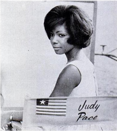 "Judy Pace on the set of her first film, The Candy Web (later called, for some reason, 13 Frightened Girls!) in 1963. This photo appeared in the May 1963 issue of Ebony and Judy and two of her co-stars appeared on the cover. The film's producer, William Castle, held contests in twelve countries to find young actresses to play teenage diplomats in the ""suspense comedy.""  He enlisted the help of Ebony to find a black actress to play the daughter of a Liberian diplomat and Pace, a finalist for Miss Bronze California of 1962, was selected. She only had six lines in the film, but she acted as the unofficial hostess to her eleven international co-stars during filming in Los Angeles."