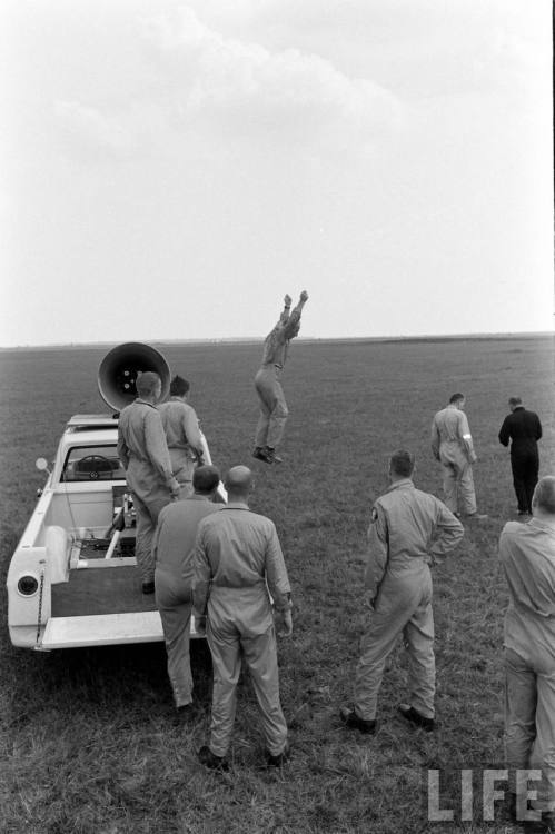 lightthiscandle:  Pete Conrad jumps off a NASA Dodge Pickup during parachute training, 1963.  Where is Scott Carpenter? Why isn't he standing on top of the van lording it over the rest of them? *le sigh of broken dreams*