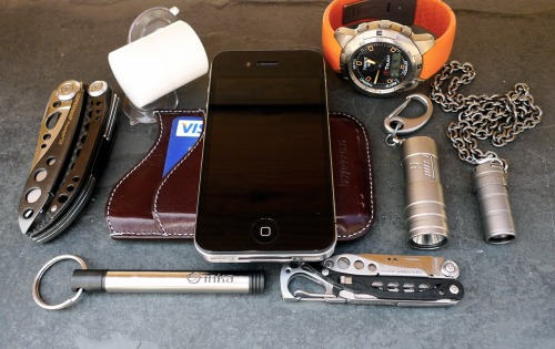 everydaycarry:  submitted by lummi  Avid follower of this very welcome blog. My current EDC, felt terribly naked whilst taking the photo. From Left - Right ish:Leatherman FreeStyle CXInka PeniStki iPhone GPS/Tripod mountiPhone 4 & BeyzacaseTissot Ti Touch Lummi Raw Ti LED torchLummi Wee Ti LED torchLeatherman Style CSMinimal but lost without any of them!  Editor's Note: Cool, I love those Lummi lights! I wanted to get a Wee back when my flashaholism was a much worse problem, but couldn't/still can't afford one :<. I can't really tell from the picture but it looks like you carry the Style and the Inka Pen loose? This isn't necessarily directed towards you but if anyone else is wondering how to carry those two together, I would try throwing a P7 suspension clip on the Inka's split ring, clipping the Leatherman to the ring, then suspending it in the front pocket. The Inka slides out of the cap and the Style can unhook from the ring, making them both accessible but in one place and not lumped at the bottom of your pocket. In any case, thanks for sharing and keep up the good work at Lummi~