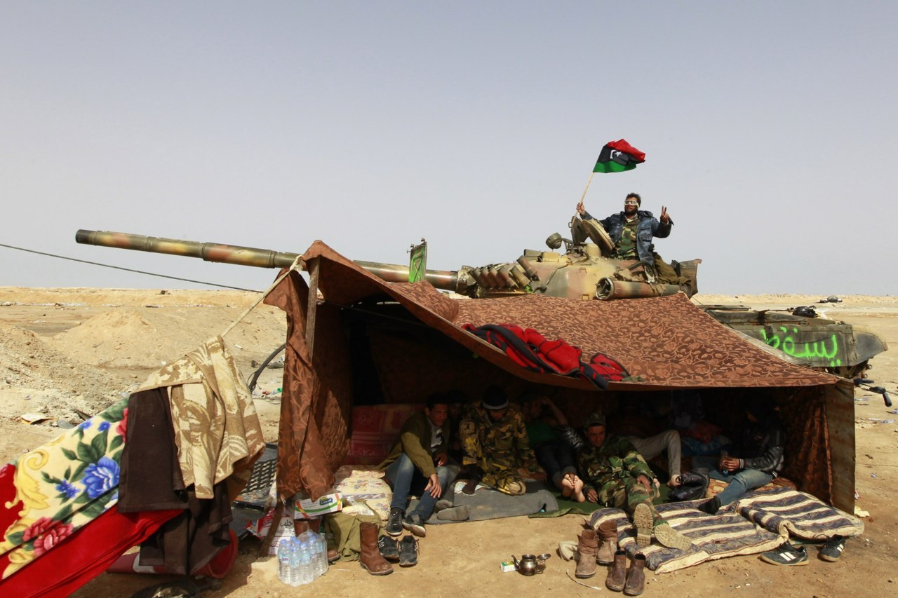 Photos of the day, April 6, 2011 Rebel fighters sit in a tent smoking hashish near a tank along the road between Ajdabiyah and Brega, Libya, April 6, 2011. (Youssef Boudlal/Reuters)