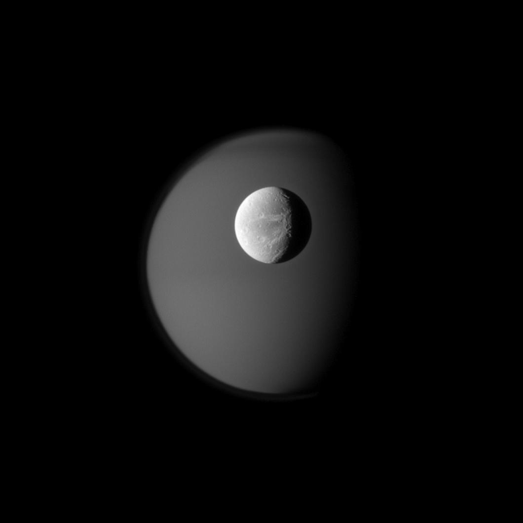 Dione and Ghostly Titan The surface of Saturn's moon Dione is rendered in crisp detail against a hazy, ghostly Titan. Credit: NASA/JPL/SSI
