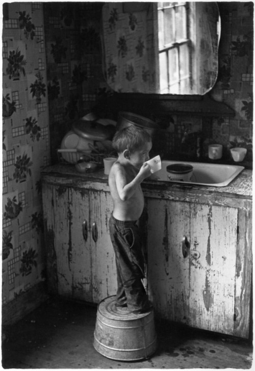 William Gedney Boy standing on washtub and drinking by kitchen sink. Kentucky, 1964. From William Gedney Photographs and Writings Duke University Rare Book, Manuscript, and Special Collections Library.