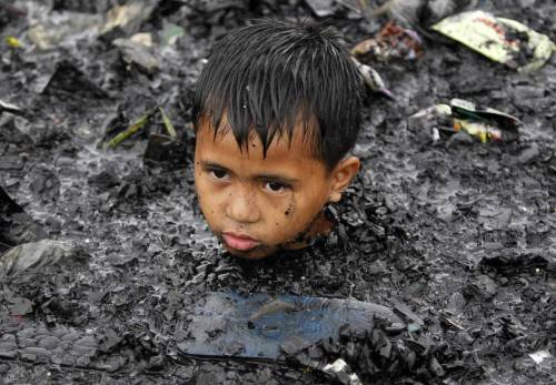 nationalpost:  Photos of the Day, April 7, 2011 A boy wades in neck-deep sea water filled with debris while searching for valuable items after a fire razed some 500 houses along a coastal village in Malabon city, north of Manila, April 7, 2011. The fire, believed to be caused by an exploding liquefied petroleum gas (LPG) tank, started before dawn on Thursday. No casualties were reported but at least 3,000 residents lost their homes. Fire fighters had a difficult time getting to the scene and putting out the blaze because the houses were close to each other and made of light materials, local media reported. (REUTERS/Erik de Castro)