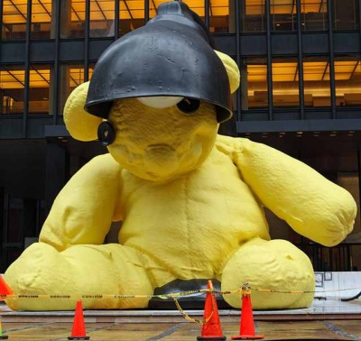 "A Giant Yellow Teddy Bear Arrives in NYC The 23-foot-tall yellow bear is called ""Untitled (Lamp/Bear)"" which is parked in front of  the Seagram Building at 375 Park Avenue, between East 52nd and East  53rd streets was created by New York-based artist Uri Fischer, and is getting auctioned off at Christie's next month. It's expected to fetch over $10 million. There are two others—one  sitting on the Montauk lawn of entrepreneur Adam Lindemann. They all  include a desk lamp that the bear is leaning against, which lights up at  night. (via Gothamist)"