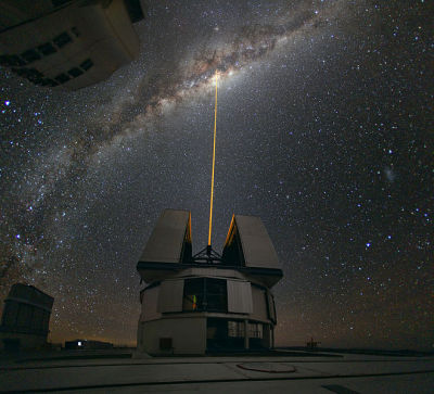 lickystickypickyme:  Real life Star Wars.Laser Towards Milky Ways Center.The color of the laser is precisely tuned to energize a layer of  sodium atoms found in one of the upper layers of the atmosphere — one  can recognize the familiar color of sodium street lamps in the color  of the laser.  This layer of sodium atoms is thought to be a leftover  from meteorites entering the Earth's atmosphere. When excited by the  light from the laser, the atoms start glowing, forming a small bright  spot that can be used as an artificial reference star for the adaptive  optics. Using this technique, astronomers can obtain sharper  observations. For example, when looking towards the center of our Milky  Way, researchers can better monitor the galactic core, where a central super massive black hole, surrounded by closely orbiting stars, is  swallowing gas and dust.  Taken with a wide angle lens, this photo covers about 180° of the sky.