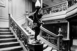 thats-not-titanic:  The Aft Grand Staircase on Olympic. Titanic's would have been almost identical, except on Titanic the lower level in this photo (B Deck) was a more open, white-paneled reception room for the A la Carte Restaurant. This room would later be added on Olympic in a different configuration, but in this photo you only see a corridor in the background.