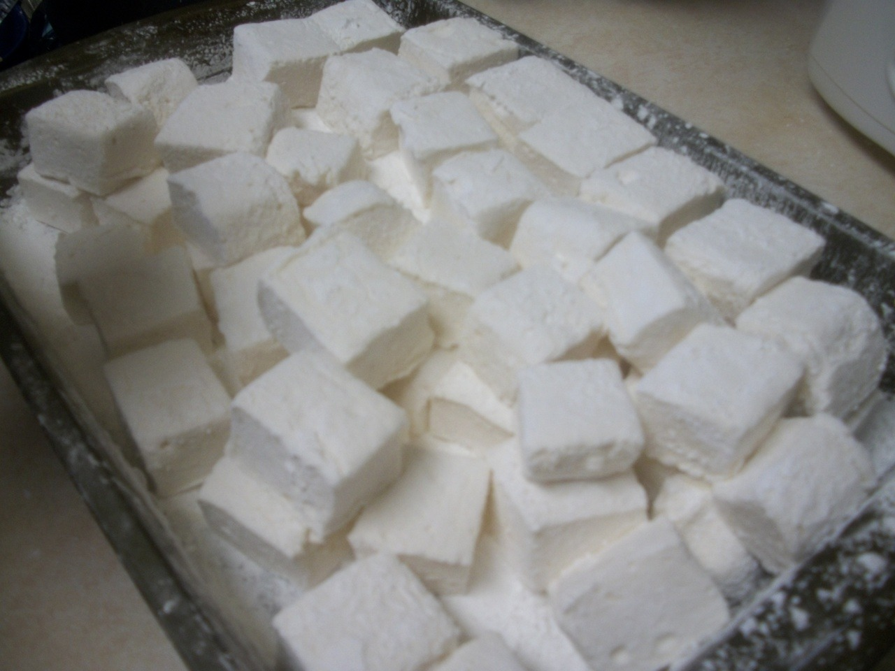 Marshmallows (from scratch) As I mentioned in my last post, anything extremely difficult, I try to make with Miki. Together we are a successful machine. We found a recipe on good ol' Smitten Kitchen. She had a hard time with it so it scared Miki and I to death because she's a pro. These were soo hard to make, not because of the possibility to screw up, but because you have so many things happening at once. If you miss a step or don't do a step fast enough, you're screwed. It was nice to have 4 hands helping out with this recipe. That being said, they are DELICIOUS! I now appreciate a marshmallow so much more that I will thank the factories that make them because there is no way I'm going to meltdown this marshmallows and make rice krispies treats with them. They are soo soft and fluffy. They have a strong vanilla taste, I bet they would taste amazing with like peppermint extract of other flavors. INGREDIENTS About 1 cup confectioners' sugar 3 1/2 envelopes (2 tablespoons plus 2 1/2 teaspoons) unflavored gelatin 1 cup cold water, divided 2 cups granulated sugar (cane sugar worked just fine) 1/2 cup light corn syrup 1/4 teaspoon salt 2 large egg whites or reconstituted powdered egg whites 1 tablespoon vanilla  Directions Oil bottom and sides of a 13- by 9- by 2-inch rectangular metal baking pan and dust bottom and sides with some confectioners' sugar (by dusting I mean a generous amount of sugar). In bowl of a standing electric mixer or in a large bowl sprinkle gelatin over 1/2 cup cold cold water, and let stand to soften. In a 3-quart heavy saucepan cook granulated sugar, corn syrup, second 1/2 cup of cold water, and salt over low heat, stirring with a wooden spoon, until sugar is dissolved.  Increase heat to moderate and boil mixture, without stirring, until a candy or digital thermometer registers 240°F, about 12 minutes.  Remove pan from heat and pour sugar mixture over gelatin mixture, stirring until gelatin is dissolved. With standing or a hand-held electric mixer beat mixture on high speed until white, thick, and nearly tripled in volume, about six minutes if using standing mixer or about 10 minutes if using hand-held mixer. (Some reviewers felt this took even longer with a hand mixer, but still eventually whipped up nicely.) In separate medium bowl with cleaned beaters beat egg whites until they just hold stiff peaks. (This took forever! I grew a few muscles during this) Beat whites and vanilla (or your choice of flavoring) into sugar mixture until just combined.  Pour mixture into baking pan and don't fret if you don't get it all out.  Sift 1/4 cup confectioners sugar evenly over top.  Chill marshmallow, uncovered, until firm, at least three hours, and up to one day. Run a thin knife around edges of pan and invert pan onto a large cutting board. Lifting up one corner of inverted pan, with fingers loosen marshmallow and ease onto cutting board.  With a large knife trim edges of marshmallow and cut marshmallow into roughly one-inch cubes.   Sift remaining confectioners' sugar back into your now-empty baking pan, and roll the marshmallows through it, on all six sides, before shaking off the excess and packing them away.