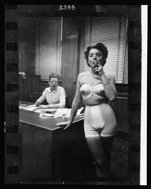 Stanley Kubrick, Lingerie model, wearing a girdle and strapless bra, smoking in an office; in the background a woman sits at a desk, Chicago, 1949
