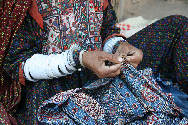 Tribal fantasy in Gujarat, India - woman sewing by Rudi Roels