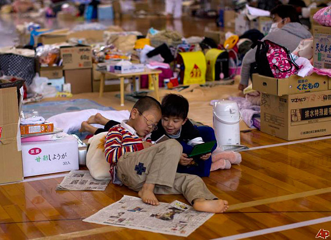 """Japanese refugee children play with their personal video games inside a gymnasium used as a shelter in Fukushima, northeastern Japan"", captured by David Guttenfelder. See also: More handholding posts [Via Associated Press, Kotaku]"