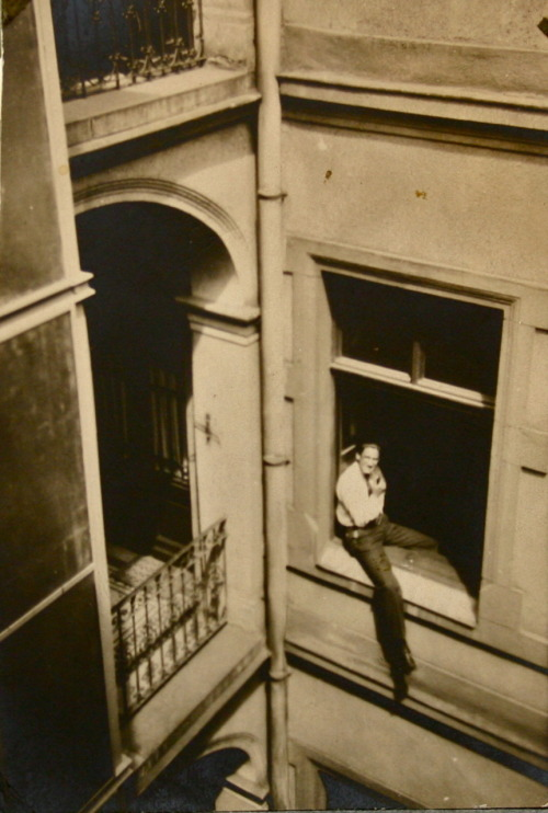 "Photo Caption: Budapest 1931  ""My family lived in a third floor apartment, in Budapest, that faced out on a busy street (now called Lenin Boulevard). It was an exciting street—colorful, crowded, noisy. There were many shops—a glamorous hardware store displaying shiny knives behind its huge plate glass front, several bookstores with books of many colors piled and strewn around, coffee houses with grouchily servile waiters carrying white napkins on their black left sleeves, and stores full of toys and candy and crutches and clothes and shoes and watches. The sidewalk was broad, and milling, crowds of people separated the shop windows from teh curb-side trees and scales (your weight for a penny) and newspaper kiosks and taxi stands. The crowds seemed always to be there—they were there when went to school early in the morning and they were there on the rare occasions when I was brought home late at night from an excursion or from a movie. Later, when I grew up, went to Hungary as an American tourist, and was out real late at night, the crowds were still there. The lights were bright and gypsy music could be heard from the coffee houses."" —Paul R. Halmos, I Want to Be a Mathematician…"