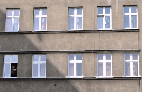 A lady cleaning windows in Krakow.