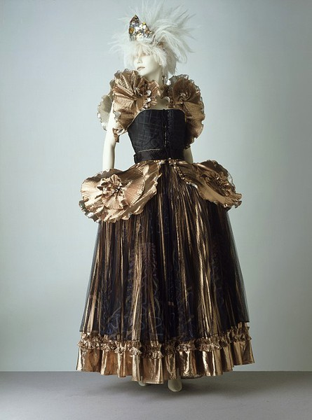 Evening Gown | Zandra Rhodes | c. 1981 Zandra Rhodes is renowned for her romantic and lavishly embellished evening clothes. In The Observer (9 October 1977) she was described as 'the most original and fearless of British designers, admired for her dedication to doing what she feels'. This innovative creation was part of her Elizabethan Collection shown in Autumn/Winter 1981. The dress can be worn in two ways, with the under-panniers used as a support for the skirt (as in the image) or with the under-panniers removed and the bodice, which has a peplum (an extension), worn outside the skirt. Zandra Rhodes studied 18th-century panniers in the V&A before completing this 'Renaissance crinoline'.