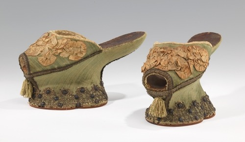 "Shoes (Chopines)1550-1650 ItalySilk, metal ""The chopine was a tall clog worn in primarily in Venice to elevate the lady above both the dirt and the hoi polloi of the street. While relatively few shoes survive from the period of the 15th to 17th century, chopines are inordinately represented in museum collections as they were saved most probably due to their outlandish peculiarity. This exemplar illustrates all the classical characteristics of this specialized form: red or green velvet covering, lobed platform sole trimmed in gold lace with hobnails, gold braid edging, shirred ribbon trim on the vamp, and beard-like tassel below the open toe."""