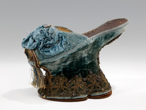 "Shoe (Chopine)1590-1610 ItalySilk, metal ""While this single chopine is very typical of the form in design and decoration, the blue color is less commonly seen than red or green. An additional feature of note also found on many other surviving examples is the leather sock lining with incised pattern of concentric squares."""