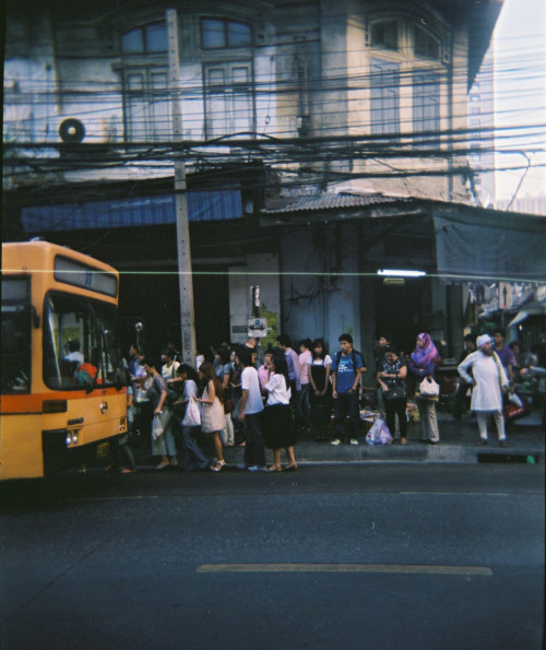 Getting on the bus. the photo is taken with my Holga on Charoen Krung road, Bangkok in 2010.