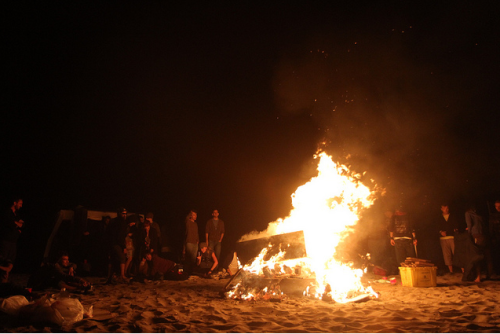 photo by mike hedge      A warm, breezy night. A bonfire on the beach. A keg of PBR. I'm in my  summer uniform—a thin racerback tank and cut-offs. My sunglasses are  still perched atop my head; I spent all day at the beach. I'm a little  drunk, now, and all of my best friends are here, but I hang back.  Sometimes it's nice to watch from afar, to enjoy a moment without being  in it. I don't want to worry about making jokes that everyone will laugh  at, I don't want to get stuck in an awkward conversation with my ex,  who I didn't know was invited.      I'm moving soon. It's time for a new town and a new adventure and I  can't help feeling that my time here has run its course. All of the  parties feel mostly the same, and my girlfriends and I have the same  conversations, over and over. My best friend is engaged, and she spends  most of her time with her fiance.      This sleepy beach town has been good to me. I came here three years ago,  and I am more confident and happier and wiser now than I was then.      I've started packing my things; I don't have much. I'll leave sometime  next week, probably. I haven't told anyone. I don't want a going away  party or tearful goodbyes. There's always phone conversations and visits  and drunken Skype sessions.  Or maybe no one will miss me all that  much, and I think that would be okay.        I'm thinking too much, and my friends are starting to glance over at me,  sitting alone in the sand. I finish my beer and I stand up, a little  unsteady on my feet. I fill my cup and I put my arm around my best  friend and kiss her cheek. She says hey, boo, and I try not to think  abut the boxes packed up in my apartment, the lease I signed for the  cute little studio apartment in Philadelphia. I crack a stupid joke, and  everyone laughs, and everything's just the way it should be.