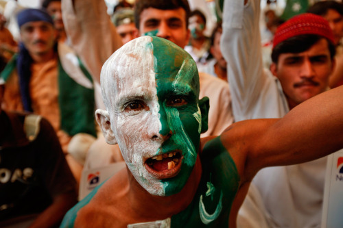 A prisoner, wearing the colors of Pakistan, celebrates an out against India from a jail in Karachi during the ICC Cricket World Cup semifinal match in India on March 30, 2011. (Athar Hussain/Reuters) #