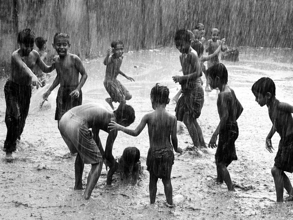nationalgeographicdaily:  Children Playing in Rain, Bangladesh Photograph by Jashim Salam Children playing in seasonal rains are a great sight of monsoon and six seasons here in Bangladesh.  The effect of climate change is making this rare as less or more rain is causing great disturbances around the country.  Heavy rain causes floods and landslides, and makes millions homeless and takes the lives of many others.  The climate should behave like normal for our future children to play like in this monsoon rains, and people must take responsibility to reduce pollution and save our world.