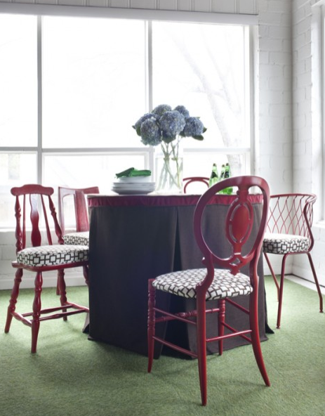 A dining room with a bunch of different chairs using the same happy red.  Great idea!