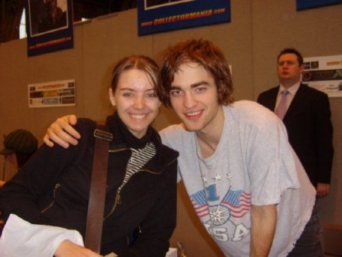 lunglock:  So, this is me and Robert Pattinson (February 2006). Pre-Twilight, I'd like to point out (very much NOT a Twilight fan). My friends and I met him at Collectormania in Manchester. It was a Sunday morning, and his queue for autograph signing was empty. So I went up, paid my £10 for a his-res print of him as Cedric Diggory, and went over to talk to him. He looked exhausted and you could tell he'd spent the whole weekend signing autographs - when no one is around he signed ones to be sold on the online store. He had a cup of coffee in front of him and a bleary look in his eyes. He's a very sweet, down to earth guy. I have no doubt he's remained this way. He spoke to us for about 10 minutes, just about where we'd come from (Swansea, in Wales). He said he'd been there once, then a few minutes later corrected himself. I can't remember where he was talking about, but he pointed out they both started with 'S' (easy mistake, Robert!). He signed my picture and I asked for a picture with him. As he stood up and put his arm around me, he said 'Sorry if I stink'. He smelt like coffee! Overall I left thinking 'What a great guy'. I'm really glad I got to meet him before the Twilight hype, because I doubt he'd be at a convetion without being swamped the whole damn time. P.S. I was so damn spotty back then, oh lordy lord.