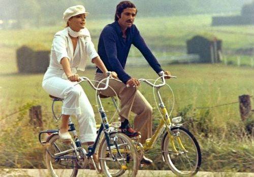 Romy Schneider and Nino Castelnuovo ride bikes.