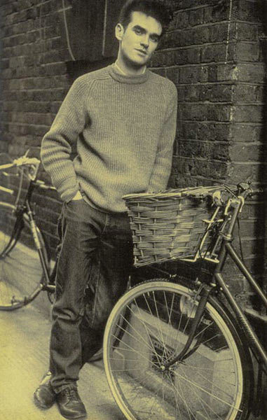 Morrissey from The Smiths posing in the street between bicycles.