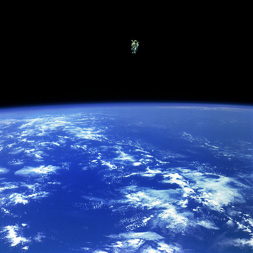 "Free Flying (by NASA Goddard Photo and Video)  Mission Specialist Bruce McCandless II, is seen further away from the  confines and safety of his ship than any previous astronaut has ever  been. This space first was made possible by the Manned Manuevering Unit  or MMU, a nitrogen jet propelled backpack. After a series of test  maneuvers inside and above Challenger's payload bay, McCandless went  ""free-flying"" to a distance of 320 feet away from the Orbiter. This  stunning orbital panorama view shows McCandless out there amongst the  black and blue of Earth and space. (02/12/1984)"