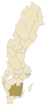 "Småland  is a historical province (landskap) in southern Sweden. Småland borders Blekinge, Scania or Skåne,Halland, Västergötland, Östergötland and the island Öland in the Baltic Sea. The name Småland literally means Small Lands. The latinized form Smolandia has been used in other languages. The highest summit in Småland is Tomtabackenwith its 377 m.   Historical cities Towns with former city status were: Eksjö (chartered around 1400), Gränna (1652), Huskvarna (1911), Jönköping (1284), Kalmar (approximately 1100), Ljungby (1936), Nybro (1932), Nässjö (1914), Oskarshamn (1856), Sävsjö (1947), Tranås (1919), Vetlanda (1920), Vimmerby(approximately 1400), Värnamo (1920), Västervik (approximately 1200), Växjö (1342)  History The area was probably populated in the Stone Age from the south, by people moving along the coast up to Kalmar. Småland was populated by Stone Age peoples by at least 6000 BC, since the Alby People are known to have crossed the ice bridge across the Kalmar Strait at that time. Migration period, Smolandian tumulus (grave mound) The name Småland (""small lands"") comes from the fact that it was a combination of several independent lands, Kinda (today a part of Östergötland), Tveta, Vista, Vedbo, Tjust, Sevede, Aspeland, Handbörd, Möre, Värend, Finnveden and Njudung. Every small land had its own law in the Viking age and early middle age and could declare themselves neutral in wars Sweden was involved in, at least if the King had no army present at the parliamentary debate. Around 1350, under the king Magnus Eriksson a national law was introduced in Sweden, and the historic provinces lost much of their old independence.  The city of Kalmar is one of the oldest cities of Sweden, and was in the medieval age the southernmost and the third largest city in Sweden, when it was a center for export of iron, which, in many cases, was handled by German merchants. Nils Dacke.18th century painting Småland was the center of several peasant rebellions, the most successful of which was Dackefejden led by Nils Dacke in 1542–1543. When officials of king Gustav Vasa were assaulted and murdered, the king sent small expeditions to pacify the area, but all failed. Dacke was in reality the ruler of large parts of Småland during the winter, though heavily troubled by a blockade of supplies, before finally being defeated by larger forces attacking from both Västergötland and Östergötland. Dacke held a famous battle defence at the (now ruined)Kronoberg Castle, and was shot while trying to escape to then Danish-ruled Blekinge.  Traditional Windsor chairs perhaps made in Småland In the 19th century, Småland was characterized by poverty, and had a substantial emigration to North America, which additionally hampered its development. The majority of emigrants ended up in Minnesota, with a geography resembling Sweden, combining arable land with forest and lakes. Max Von Sydow and Liv Ullman from the film ""The Emigrants"" (novel by V.Moberg) An image from a canyon in the forested Småland. Religion In comparison with much of Sweden, Småland has a higher level of religious intensity and church participation (Lutheran). Smalandians In the 20th century, Småland has been known for its high level of entrepreneurship and low unemployment, especially in the Gnosjöregion. Some suggest the harsh conditions have throughout history forced the inhabitants of the region to be cunning, inventive and cooperative. This is how the old Swedish encyclopedia Nordisk familjebok described the people: the Smalandian is by nature awake and smart, diligent and hard-working, yet compliant, cunning and crafty, which gives him the advantage of being able to move through life with little means. A running joke, or stereotype, in Sweden, is that of the Smalandian being very economical, or even cheap. Ingvar Kamprad said that the Smalandian are seen as the Scotsmen of Sweden. Language The local language is a Swedish dialect known as Småländska (Smalandian). This may in turn be separated in two main branches, with the northern related to the Götaland dialects and the southern to the Scanian dialects. Heraldry  The first coat of arms for Småland, granted in 1560 pictured a red crossbow with roses on a golden shield but at the coronation ofJohan III in 1569 a new coat of arms was granted. A lion was wielding the crossbow and the roses had fallen off. There was also a revision in 1944, but no alterations were made. Småland is also considered a duchy and has the right to carry a ducal coronet with the arms. Blazon: ""Or a lion rampant Gules langued and armed Azure holding in front paws a Crossbow of the second bowed and stringed Sable with a bolt Argent."""