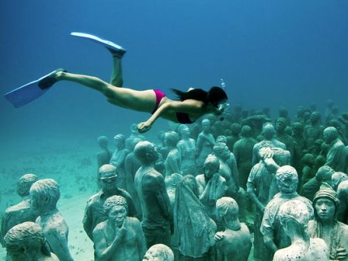 "Visitor from Above by Jason deCaires Taylor  ""Created by Mexico-based British sculptor Jason deCaires Taylor, the Caribbean installation is intended to eventually cover more than 4,520 square feet (420 square meters), which would make it ""one of the largest and most ambitious underwater attractions in the world,"" according to a museum statement.  In doing so, Taylor hopes the reefs, which are already stressed by marine pollution, warming waters, and overfishing, can catch a break from the approximately 750,000 tourists who visit local reefs each year.  ""That puts a lot of pressure on the existing reefs,"" Taylor told National Geographic News. ""So part of this project is to actually discharge those people away from the natural reefs and bring them to an area of artificial reefs.'"""