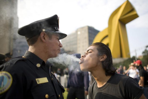 APTOPIX Mexico Massacre Anniversary A  protester blows marijuana smoke in the face of a police officer during a  march to mark the 1968 Tlatelolco plaza massacre in Mexico City