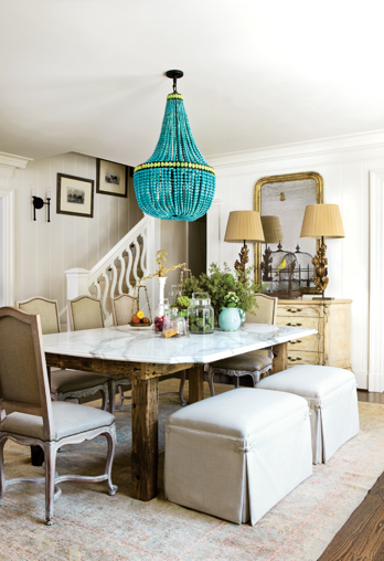 A neutral, traditional style dining room gets a vibrant punh of color with a stuning turquoise chandelier.