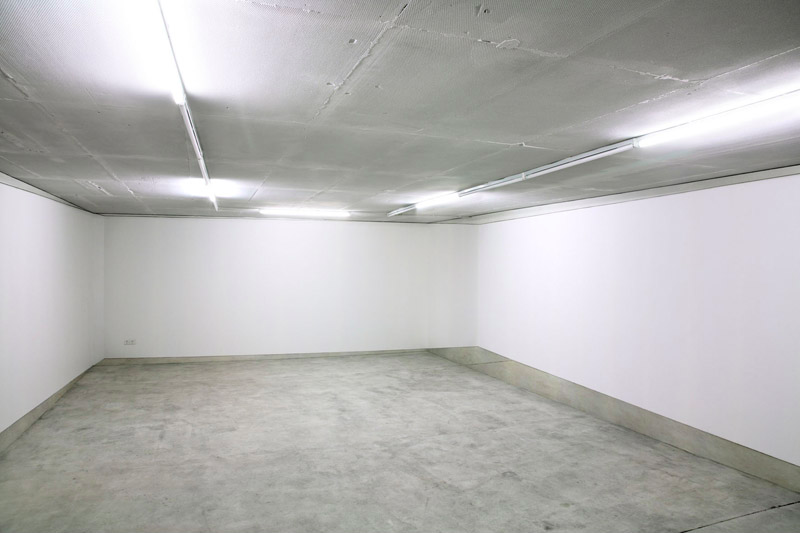 Room by Daniela Friebel: A room with four, empty, white walls covered with a photographic wallpaper that shows an exact image of that room - slightly shifted. An illusionary room that expresses a changed architectural situation, and whose perspective works correctly only from one specific point in the room.