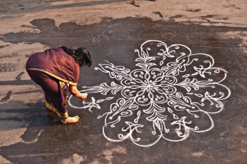 dopatonin:  Kolam is a form of sand painting that is drawn using rice powder by female members of the family in front of their home. It is widely practiced by Hindus in South India. A kolam is a sort of painted prayer - a line drawing composed of curved loops, drawn around a grid pattern of dots. Kolams are thought to bestow prosperity to homes.